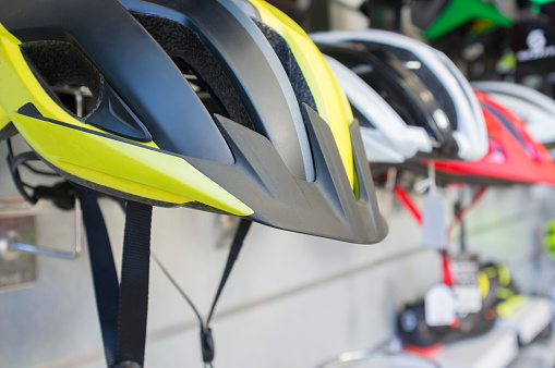 New bike helmets displayed on shop. Painted with reflecting color highly visible