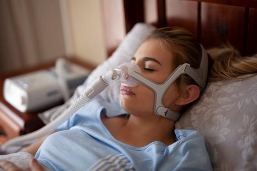 Woman in bed wearing CPAP machine for sleep apnea